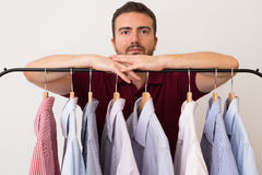 Man choosing shirts in several colors and textures Stock Photography