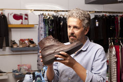 Man choosing shoes during footwear shopping at shoe shop Stock Images