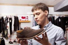 Man choosing shoes during footwear shopping at shoe shop. Young man choosing shoes during footwear shopping at shoe shop Royalty Free Stock Photos