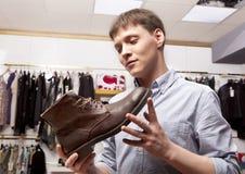 Man choosing shoes during footwear shopping at shoe shop Stock Photo