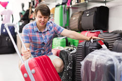 Man choosing suitcase at the store. Smiling young male choosing new suitcase at the store Royalty Free Stock Image
