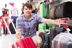 Man choosing suitcase at the store. Smiling young man choosing suitcase in the shop Stock Images