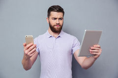 Man choosing between tablet computer and smartphone. Portrait of a young man choosing between tablet computer and smartphone over gray background Stock Image