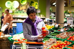 Man choosing tomatoes in a fresh food section Stock Photos