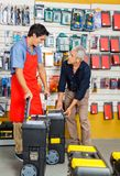 Man Choosing Tool Cases While Salesman Assisting. Senior men choosing tool cases while salesman assisting him in hardware store Royalty Free Stock Photography