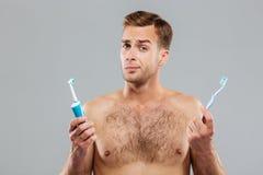 Man choosing toothbrush over gray background Stock Photo