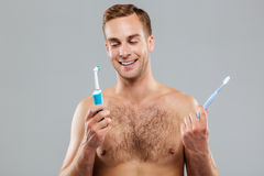 Man choosing toothbrush over gray background Royalty Free Stock Photo