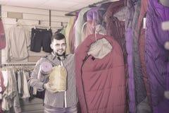 Man choosing touristic equipment in sports equipment store Stock Photos