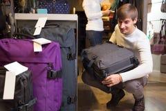 Man choosing travel suitcase in haberdashery shop Royalty Free Stock Image