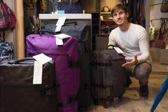 Man choosing travel suitcase in haberdashery shop Stock Image
