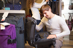 Man choosing travel suitcase. Young male choosing travel suitcase in haberdashery shop Royalty Free Stock Photo
