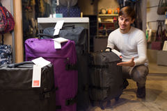 Man choosing travel suitcase. Young male choosing new travel suitcase in haberdashery shop Stock Image