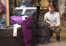Man choosing travel suitcase. Young male choosing new travel suitcase in haberdashery shop Royalty Free Stock Photography