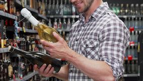 Man choosing between two bottles of wine. Cropped shot of a male customer smiling while choosing wine to buy. Bearded man shopping at the drinks department at royalty free stock images