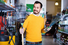 Man choosing various tools in garden equipment shop royalty free stock photography