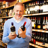 Man choosing wine. Man in a supermarket choosing the right wine Royalty Free Stock Photos