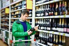Man choosing wine in supermarket Stock Images