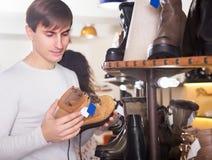 Man choosing winter shoes. Happy man choosing winter shoes in a shoe store stock photography