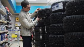 Man choosing winter tires in the automotive store. Young man looking over automobile winter tyres in the automotive department of the hypermarket stock footage