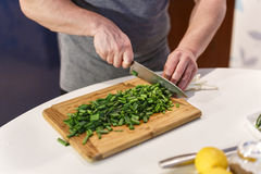 Man chopped green onion on the board Stock Image