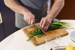 Man chopped green onion on the board Royalty Free Stock Image