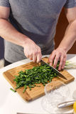 Man chopped green onion on the board Stock Photos