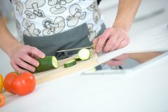 Man chopping cucumber with kitchen knife. Man chopping cucumber with a kitchen knife Stock Images