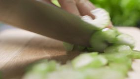 Man chopping fresh celery on wooden board with sharp knife close up.  stock footage