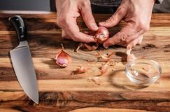 Chopping Shallots For Dinner. A man chopping fresh shallots on a wooden cutting board Stock Photos