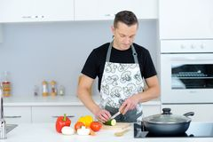 Man chopping vegetables in kitchen Stock Photos