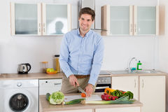 Man Chopping Vegetables In Kitchen Royalty Free Stock Photo