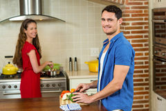 Man chopping vegetables and woman cooking on stove Royalty Free Stock Image