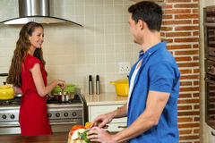 Man chopping vegetables and woman cooking on stove Stock Images