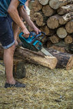 Man chopping wood with a chainsaw Royalty Free Stock Image