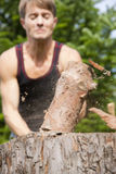 Man chopping wood in his garden. Man in his garden chopping wood using an axe, the setting is in summer, focus on the wood and lots of motion blur as the wood is Stock Image