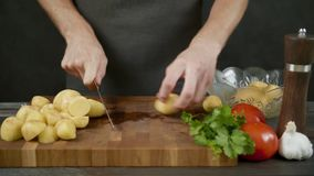 Man chops potatoes on wooden cutting board isolated in kitchen black background. Man chops potatoes on the wooden cutting board isolated in kitchen black stock video footage