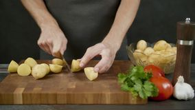Man chops potatoes on wooden cutting board isolated in kitchen black background. Man chops potatoes on the wooden cutting board isolated in kitchen black stock footage