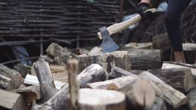 Man chops wood outdoors in slow motion. Man`s hands working with ax. A man woodcutter chops tree trunks with an ax for. Chopping wood with ax in slow motion stock footage