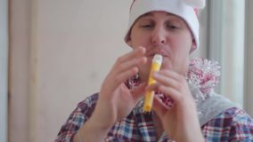 Man in Christmas cap plays the flute stock footage
