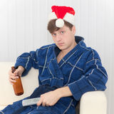 Man in Christmas cap with remote control and beer Royalty Free Stock Images