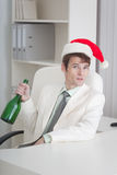 Man in Christmas cap sits with bottle at table Stock Images