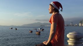 Man in the Christmas cap sits on the railing and looking at fishing boas in sea and raising sun. Asia. Vietnam. Christmas. New Year stock video footage