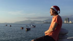 Man in the Christmas cap sits on the railing and looking at fishing boas in sea and raising sun. Asia. Vietnam. Christmas. New Year stock footage