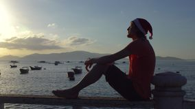 Man in the Christmas cap sits on the railing and looking at fishing boas in sea and raising sun. Asia. Vietnam. Christmas. New Year stock video