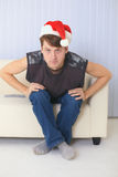 Man in Christmas cap sits on sofa and watches TV Stock Photography