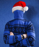 Man in christmas hat. Man in blue sweater and red chrismas hat at blue background Stock Photos