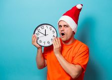 Man with Christmas hat and big clock. Young handsome man in orange t-shirt with Christmas hat and big clock. Studio image on blue background Royalty Free Stock Photography