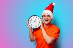 Man with Christmas hat and big clock. Young handsome man in orange t-shirt with Christmas hat and big clock. Studio image on blue background Stock Images