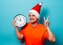 Man with Christmas hat and big clock. Young handsome man in orange t-shirt with Christmas hat and big clock. Studio image on blue background Stock Photos