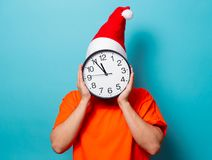 Man with Christmas hat and big clock. Young handsome man in orange t-shirt with Christmas hat and big clock. Studio image on blue background Stock Photo